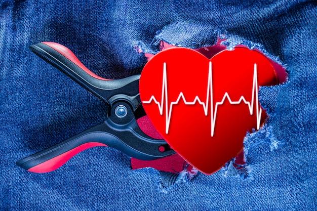 Herz mit ekg-linien, die in einer medizinischen wiederbelebungszange vor dem hintergrund eingeklemmt sind