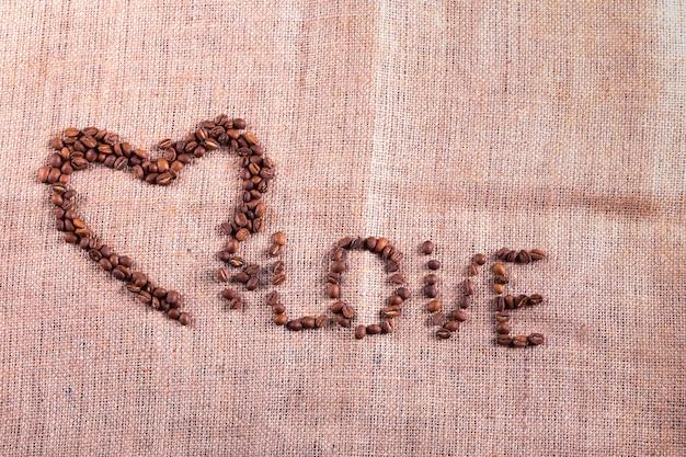 Herz mit gerösteten kaffeebohnen auf dem sackleinenhintergrund