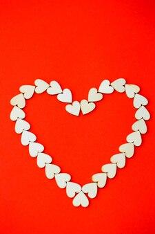 Herz mit holzherzen auf einem leuchtend roten hintergrund gesäumt. platz für eine inschrift, romantisches bild zum valentinstag