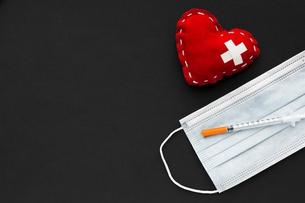 Herz mit spritze auf staubmaske