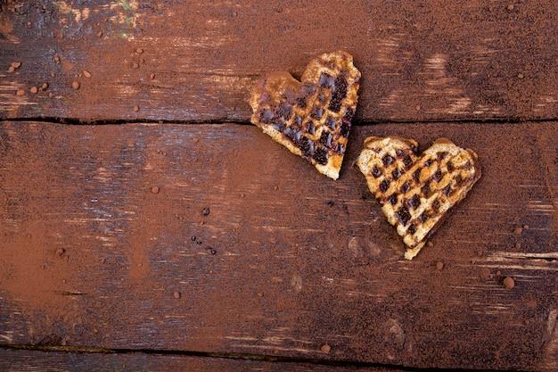 Herz mit zwei belgiern formte waffel mit schokolade auf hölzernem hintergrund. flach liegen. kopieren sie platz