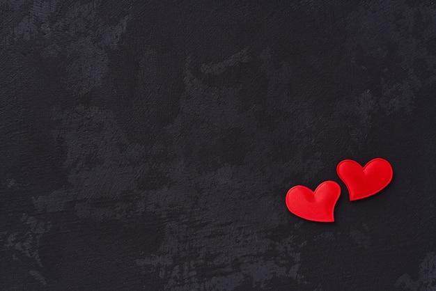Herz mit zwei rottönen auf schwarzem hintergrund. ansicht von oben
