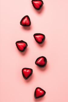 Herz rote süßigkeiten, liebesbrief und geschenk auf blau. romantische einladung zum valentinstag.