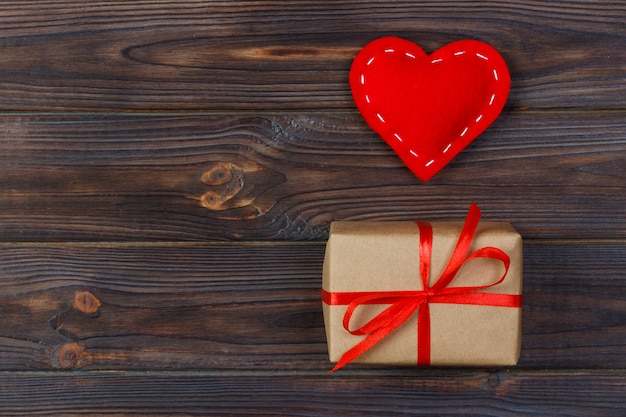 Herz und geschenkbox mit rotem band auf hölzernem hintergrund