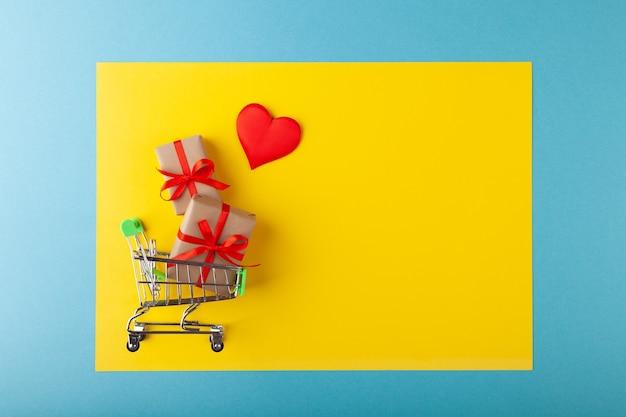 Herz und geschenkbox mit rotem band innerhalb des mini-einkaufswagens auf gelbem und blauem hintergrund, verkaufs- und liebeskonzept, valentinstag, kopienraum, horizontal
