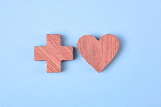 Herz und kreuz, hölzerne ikonen, die durch einen rosa fleck auf einem hellblauen hintergrund getönt werden