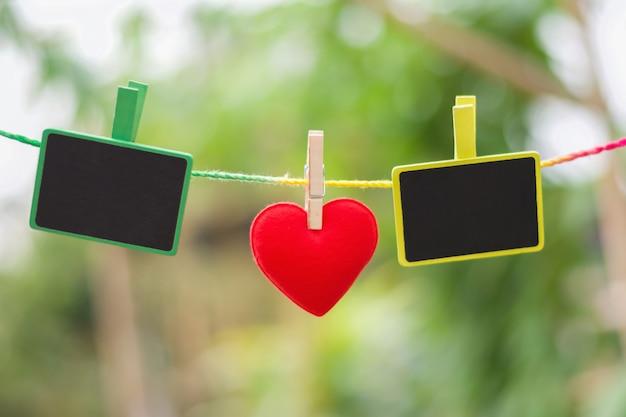 Herz und leeres holz hängen am seil. konzept valentinstag
