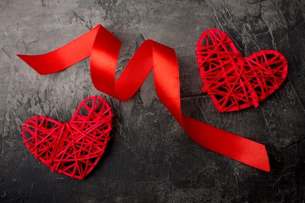 Herz und rotes band auf einem dunklen hintergrund. valentinstag oder hochzeit. sicht von oben