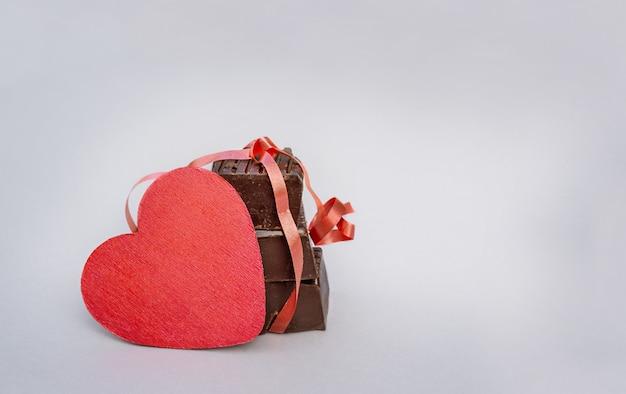 Herz und schokolade. roter herzkopierraum und schokoladenstücke auf grauem hintergrund