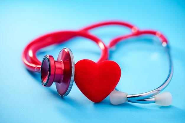 Herz und stethoskop auf blauem hintergrund. selektiver fokus.