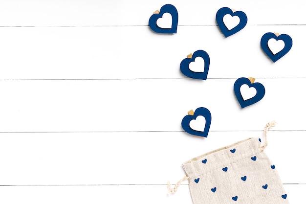 Herz und tasche auf weißer holzoberfläche. valentinstag konzept. trendige farbe