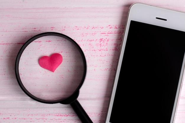 Herz unter der lupe in der nähe eines mobiltelefons