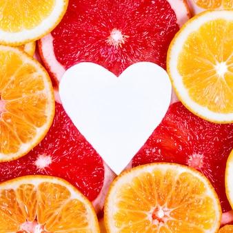 Herz unter zitrusfrüchten. zitrone, orange, grapefruit auf weißem hintergrund