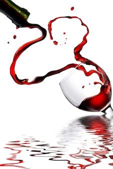 Herz vom eingießen von rotwein in becher lokalisiert auf weiß