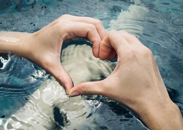 Herz von den händen auf swimmingpool
