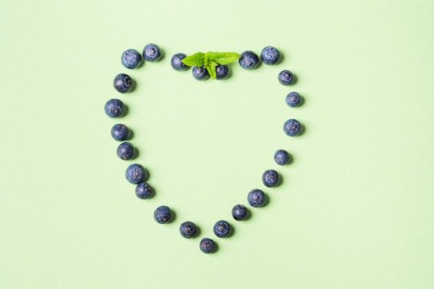 Herz von frischen blaubeeren auf pastellgrün