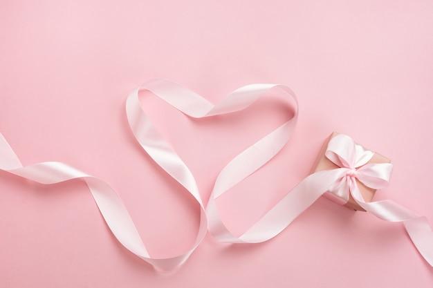 Herz von rosa band und geschenkbox auf pastellrosa hintergrund. valentinstag komposition.