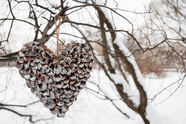 Herz von skalen von den kiefernkegeln, die am baum am weißen winter hängen.