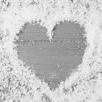Herz zwischen dekorativem schnee auf hölzernem schreibtisch