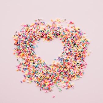 Herz zwischen verschiedenen bunten bonbons