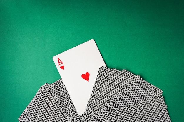 Herzass mit spielkarten auf grünem hintergrund. freier platz für text
