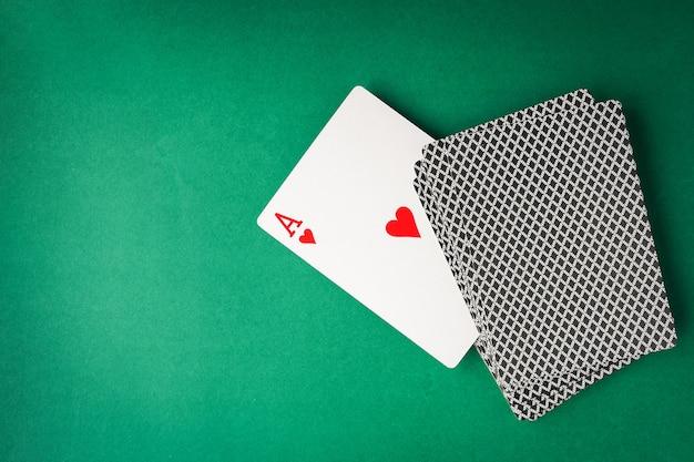 Herzass mit spielkarten auf grünem hintergrund.