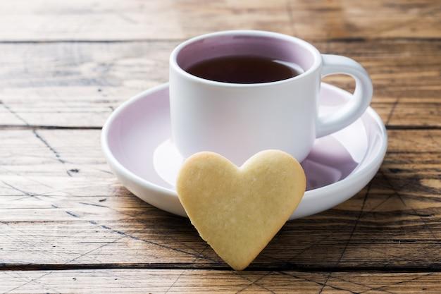 Herzausgangsplätzchen und -tasse kaffee auf einer platte