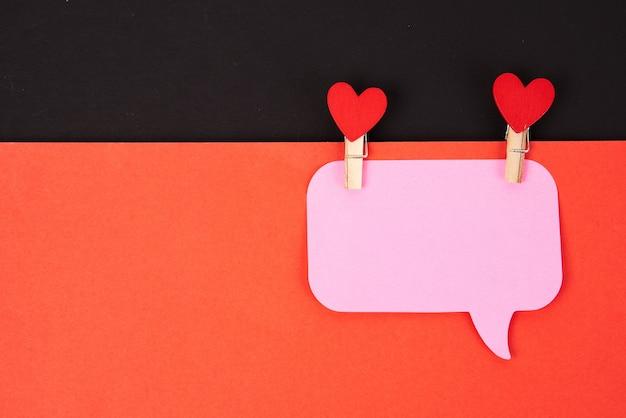 Herzen auf einer wäscheklammer auf rotem papier