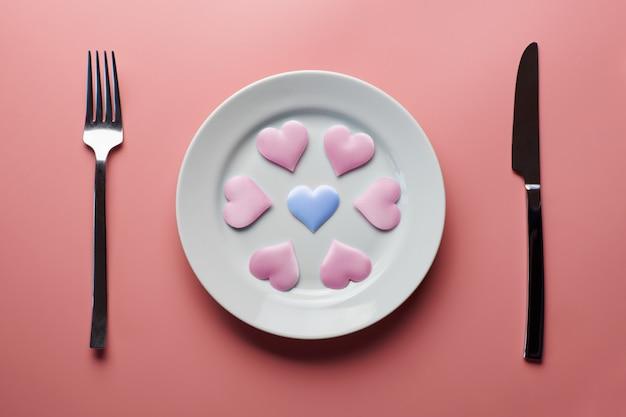 Herzen auf platte auf rosa hintergrund
