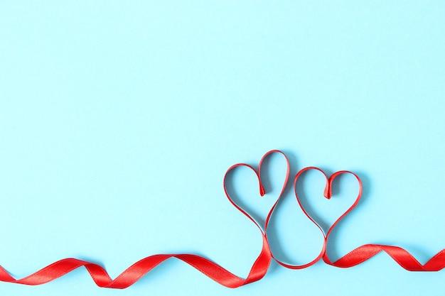 Herzen aus bändern auf einem farbigen hintergrund draufsicht