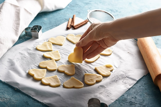 Herzen aus teig auf pergamentpapier mit hand auf blauem hintergrund. prozess des kochens von keksen konzept