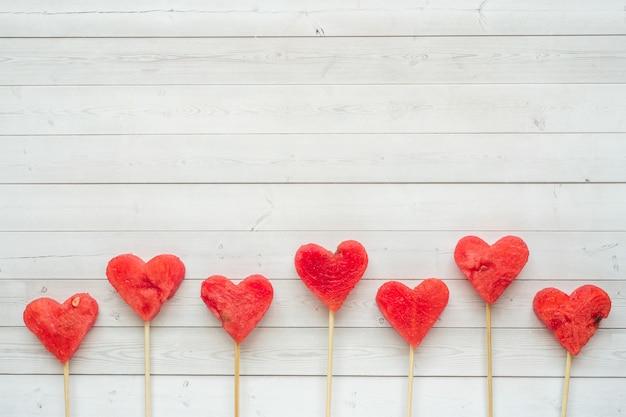 Herzen aus wassermelone am stiel geschnitzt. konzept des valentinsgrußes