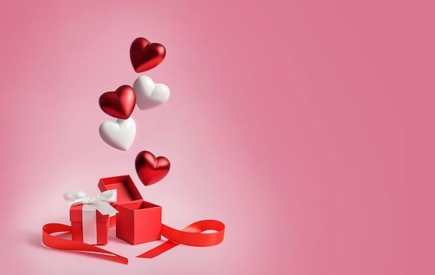 Herzen fallen in geschenkboxen. valentinstagskonzept auf einer rosa oberfläche. Premium Fotos
