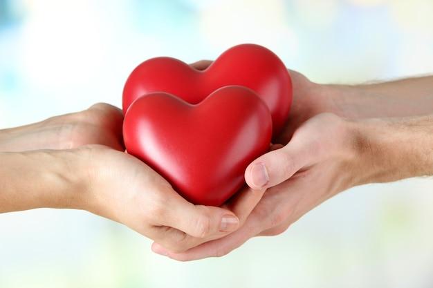 Herzen in den händen auf hellem hintergrund
