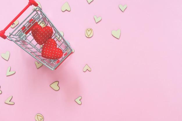 Herzen in der einkaufswagenlaufkatze auf rosa hintergrund