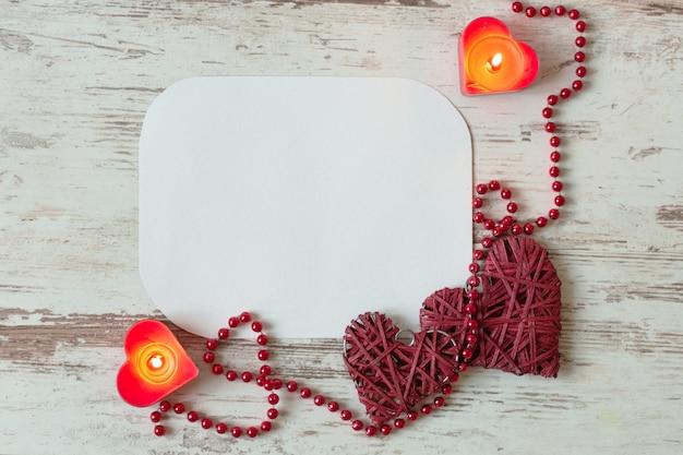 Herzen mit roter perlenkette und kerzen auf holztisch. leere grußkarte zum valentinstag