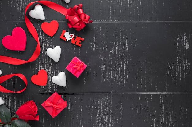 Herzen und geschenke auf schwarzem hintergrund