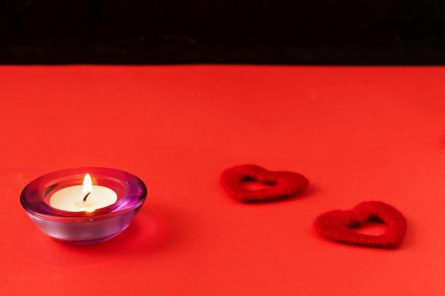 Herzen und kerze auf rotem grund