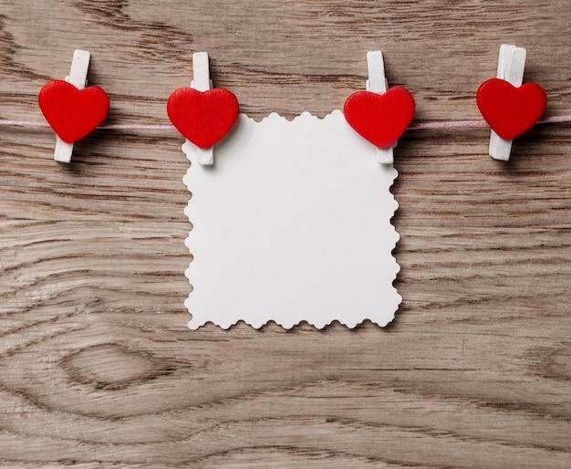 Herzen und leere notiz auf der wäscheklammer auf hölzernem hintergrund