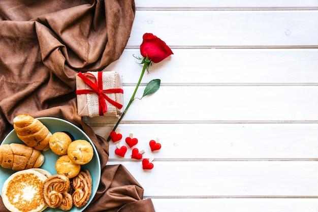 Herzen und rose in der nähe von geschenk und gebäck