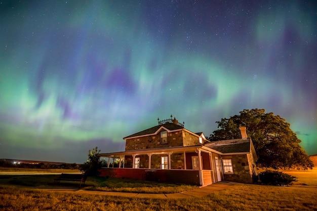 Herzförmige aurora borealis über dem historischen goodwin house in saskatchewan, kanada