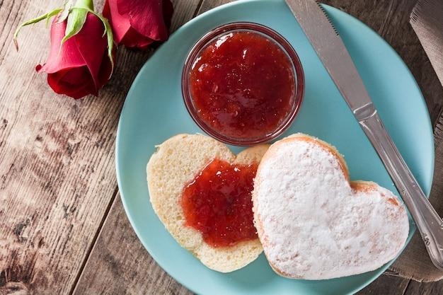 Herzförmige brötchen- und beerenmarmelade des valentinstagfrühstücks draufsicht