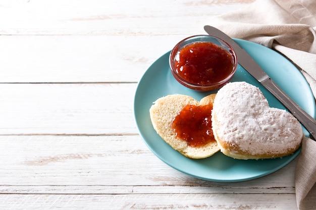 Herzförmige brötchen- und beerenmarmelade des valentinstagfrühstücks, kopienraum