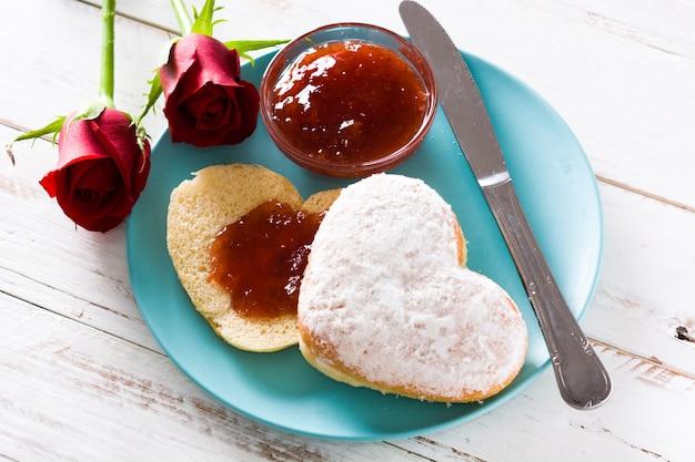 Herzförmige brötchen- und beerenmarmelade des valentinstagfrühstücks
