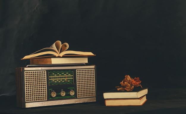 Herzförmige bücher auf retro-radio-empfänger mit getrockneten blumen auf ihnen platziert