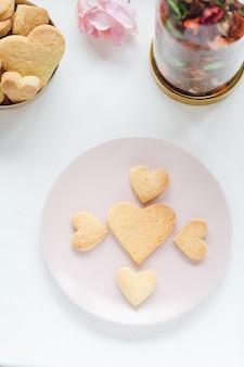 Herzförmige butterkekse auf einem rosa teller und rose auf dem tisch valentinstag-konzept