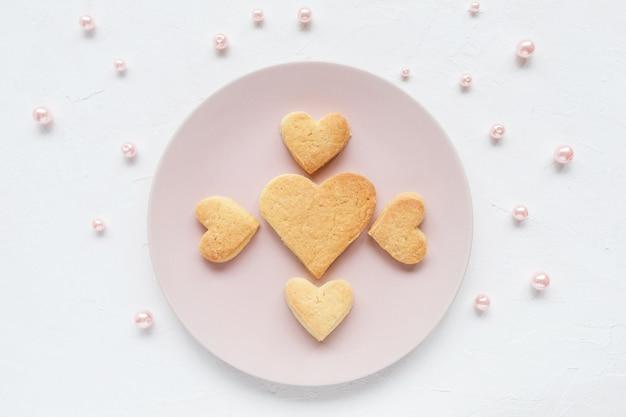 Herzförmige butterplätzchen auf einer rosa platte