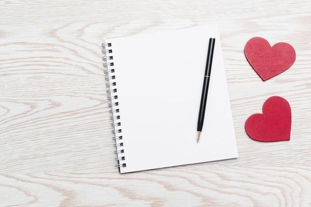 Herzförmige dekorationen mit leerem notizbuch und stiftkomposition für valentinstag, hölzerner hintergrund mit kopienraum