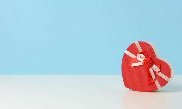 Herzförmige geschenkbox aus rotem karton auf weißem tisch, festlicher hintergrund, kopierraum