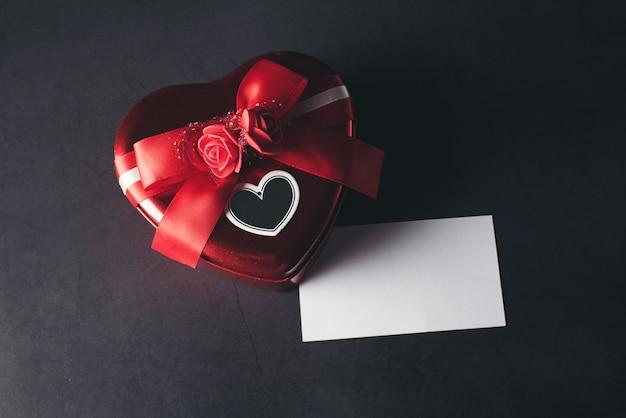Herzförmige geschenkbox mit leerer anmerkungskarte, valentinsgrußtag
